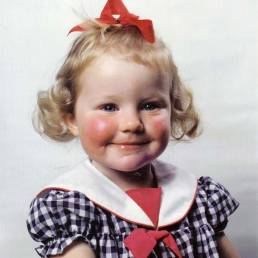 Erin at an early age with a head full of ribbons, curls and rosy cheeks!